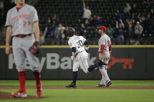 Seattle Mariners' Kyle Lewis (30) rounds the bases past Cincinnati Reds starting pitcher Trevor Bauer, left, and Reds' Jose Peraza, right, after Lewis hit a solo home run during the fifth inning of a baseball game Tuesday, Sept. 10, 2019, in Seattle during the second at-bat of his major league debut. (AP Photo/Ted S. Warren)