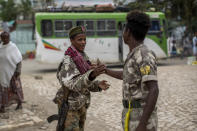 Fighters loyal to the Tigray People's Liberation Front (TPLF) greet each other on the street in the town of Hawzen, then-controlled by the group, in the Tigray region of northern Ethiopia, on Friday, May 7, 2021. The rural town is a microcosm of the challenge facing Prime Minister Abiy Ahmed _ and a warning that the war here is unlikely to end anytime soon. (AP Photo/Ben Curtis)