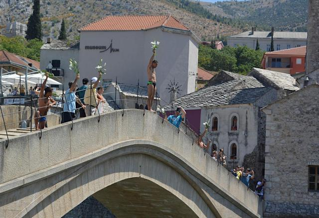 "<p>A man holding flowers in his hand jumps into the Neretva river from historical ""Old Bridge"", also known as ""Mostar Bridge"" to mark the 22nd anniversary of the 1995 Srebrenica genocide in Mostar, Bosnia and Herzegovina on July 11, 2017. (Photo: Zeljko Milicevic/Anadolu Agency/Getty Images) </p>"
