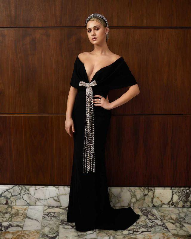 <p>wears a Prada gown with a crystal embellished bow and Lorraine Schwartz jewelry. </p>
