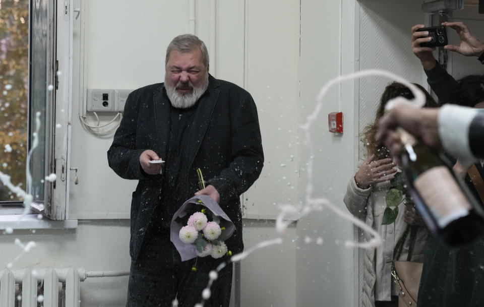 Colleagues pour champagne on Novaya Gazeta editor Dmitry Muratov at the Novaya Gazeta newspaper, in Moscow, Russia, Friday, Oct. 8, 2021. The 2021 Nobel Peace Prize has been awarded to journalists Maria Ressa of the Philippines and Muratov of Russia. The Norwegian Nobel Committee cited their fight for freedom of expression, stressing that it is vital in promoting peace. (AP Photo/Alexander Zemlianichenko)