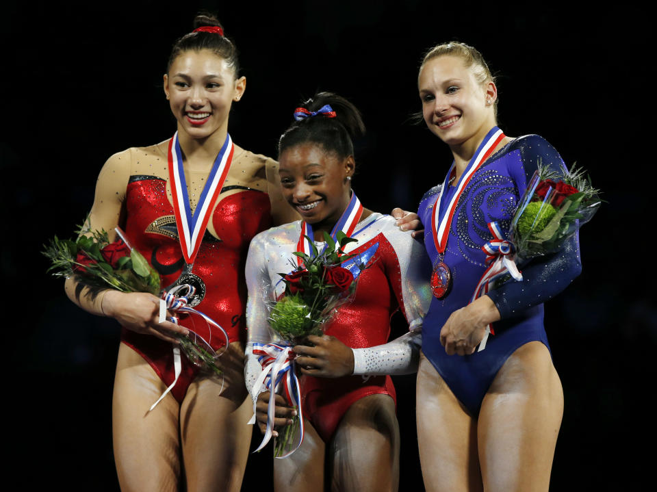 Simone Biles, center, reacts during the medals ceremony at the U.S. women's national gymnastics championships in Hartford, Conn., Saturday, Aug. 17, 2013. Biles won the gymnastics title, edging Kyla Ross, left, who came in second. Third-place finisher Brenna Dowell, right, smiles. (AP Photo/Elise Amendola)