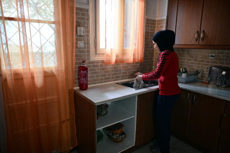 A Syrian woman washes dishes in an apartment in Athens where over one million euros has been injected into the economy via a refugee housing programme (AFP Photo/LOUISA GOULIAMAKI)