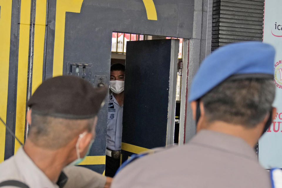 Staff and police officers guard the main entrance gate of Tangerang prison in Tangerang on the outskirts of Jakarta, Indonesia, Wednesday, Sept. 8, 2021. A massive fire raged through the overcrowded prison early Wednesday, killing a number of inmates. (AP Photo/Dita Alangkara)