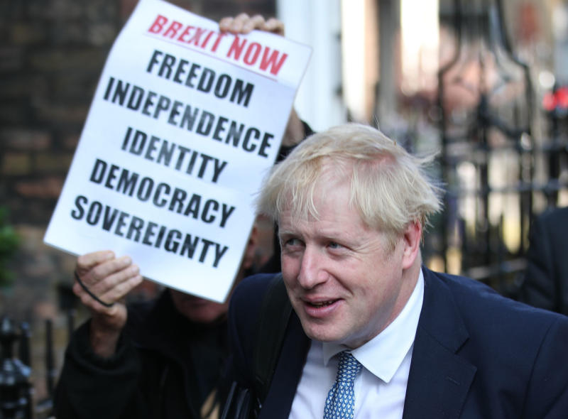Conservative party leadership contender Boris Johnson, is shadowed by a Brexit demonstrator, as he arrives at his office in central London, Tuesday July 23, 2019. Britain's governing Conservative Party is set to reveal the name of the country's next prime minister later Tuesday, with Brexit champion Boris Johnson widely considered to be favourite to get the job against fellow contender Jeremy Hunt. (Yui Mok/PA via AP)