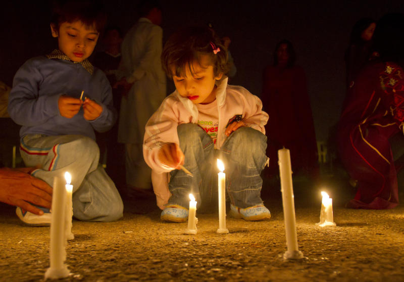 Pakistani children light candles during a ceremony to mark Earth Hour in Islamabad, Pakistan, on Saturday, March 31, 2012. Earth Hour takes place worldwide at 8.30 p.m. local times and is a global call to turn off lights for 60 minutes in a bid to highlight the global climate change. (AP Photo/Anjum Naveed)