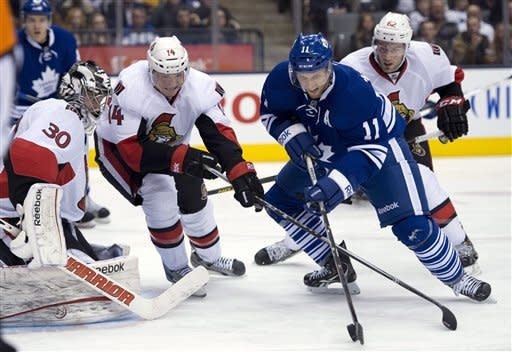 Toronto Maple Leafs centre Jay McClement (11) tries to shoot on Ottawa Senators goaltender Ben Bishop (3) as left winger Colin Greening (14) tries to break up the play during second-period NHL hockey game action in Toronto, Wednesday, March 6, 2013. (AP Photo/The Canadian Press, Frank Gunn)