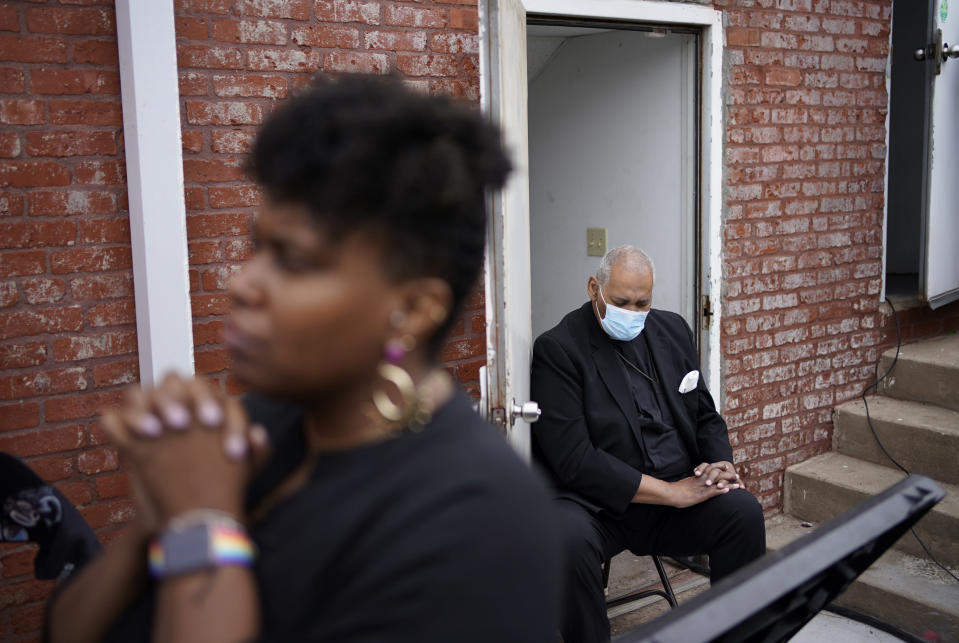 People pray during the dedication of a prayer wall at the historic Vernon African Methodist Episcopal Church in the Greenwood neighborhood during the centennial of the Tulsa Race Massacre, Monday, May 31, 2021, in Tulsa, Okla. The church was largely destroyed when a white mob descended on the prosperous Black neighborhood in 1921, burning, killing, looting and leveling a 35-square-block area. (AP Photo/John Locher)