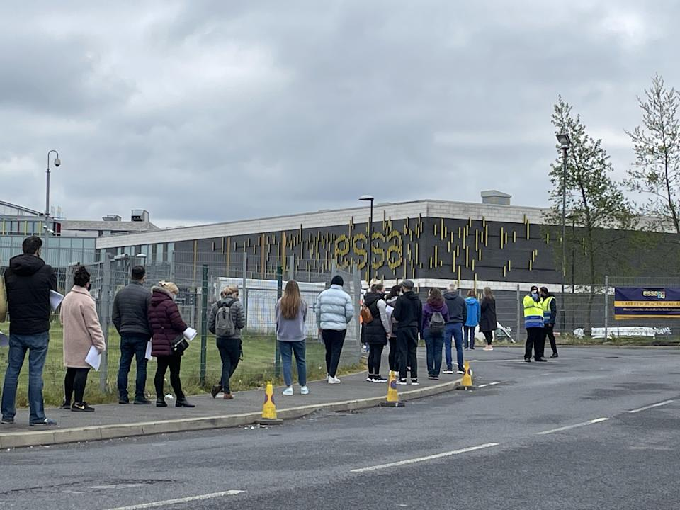 <p>People queue outside a vaccination centre</p> (PA Wire)