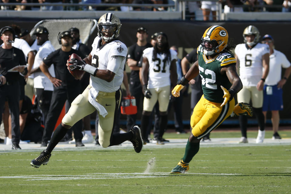New Orleans Saints quarterback Jameis Winston, left, scrambles away from Green Bay Packers linebacker Rashan Gary (52) as he looks for a receiver during the first half of an NFL football game, Sunday, Sept. 12, 2021, in Jacksonville, Fla. (AP Photo/Stephen B. Morton)