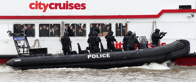 Hostages put their hands up inside the boat as firearms officers attempt to board in a mock anti-terror training exercise (PA)