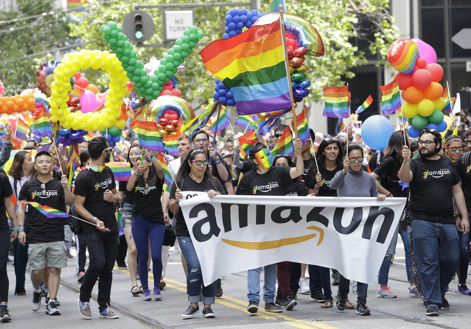 FILE - In this June 25, 2017 file photo, a group with Amazon marches in the Pride parade in San Francisco. More than 400 companies, including Amazon, have signed on to support civil rights legislation for LGBTQ people that is moving through Congress, advocates said Tuesday, April 27, 2021. The Equality Act would amend existing civil rights law to explicitly include sexual orientation and gender identification as protected characteristics. (AP Photo/Jeff Chiu, File)