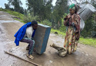 """Senait Ambaw, right, who said her home had been destroyed by artillery, leaves by foot on a path near the village of Chenna Teklehaymanot, in the Amhara region of northern Ethiopia Thursday, Sept. 9, 2021. At the scene of one of the deadliest battles of Ethiopia's 10-month Tigray conflict, witness accounts reflected the blurring line between combatant and civilian after the federal government urged all capable citizens to stop Tigray forces """"once and for all."""" (AP Photo)"""
