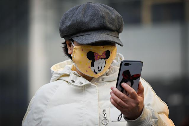 A woman is pictured wearing a Minnie Mouse face mask in Beijing on 11 February. (Getty)