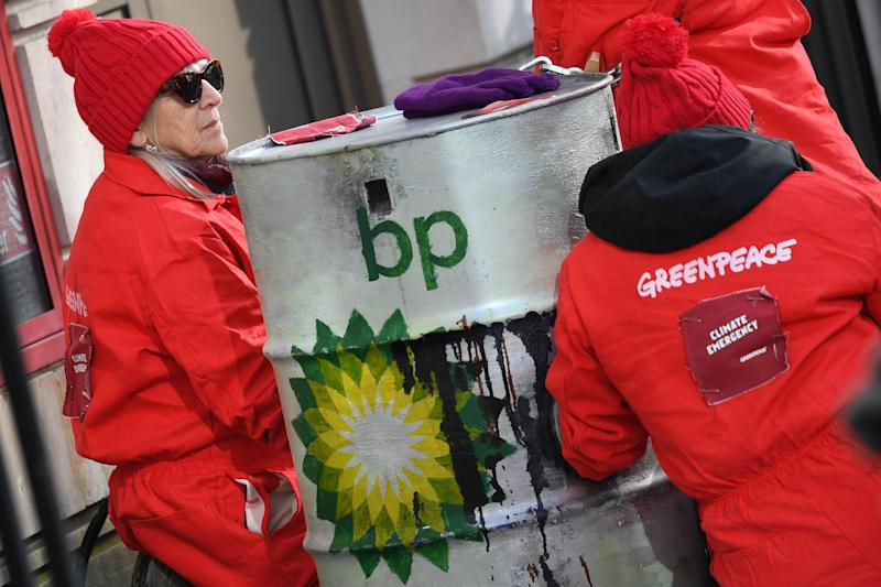 Greenpeace activists sit chained into oil barrels as they protest outside the headquarters of oil giant BP in London on February 5, 2020, on the day that the company's new was set to take up his role. - Activists from Greenpeace on Wednesday blocked the headquarters of BP in London with solar panels and mock barrels of crude to mark the first day of the oil giant's new CEO, Bernard Looney. (Photo by DANIEL LEAL-OLIVAS / AFP) (Photo by DANIEL LEAL-OLIVAS/AFP via Getty Images)