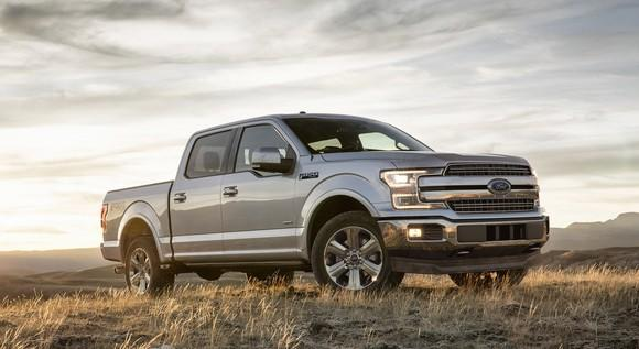 A silver Ford F-150 pickup in a field.