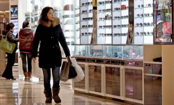 "A woman shops in a Beijing mall: ""The economy has officially exited its slowdown,"" Chinese officials said."