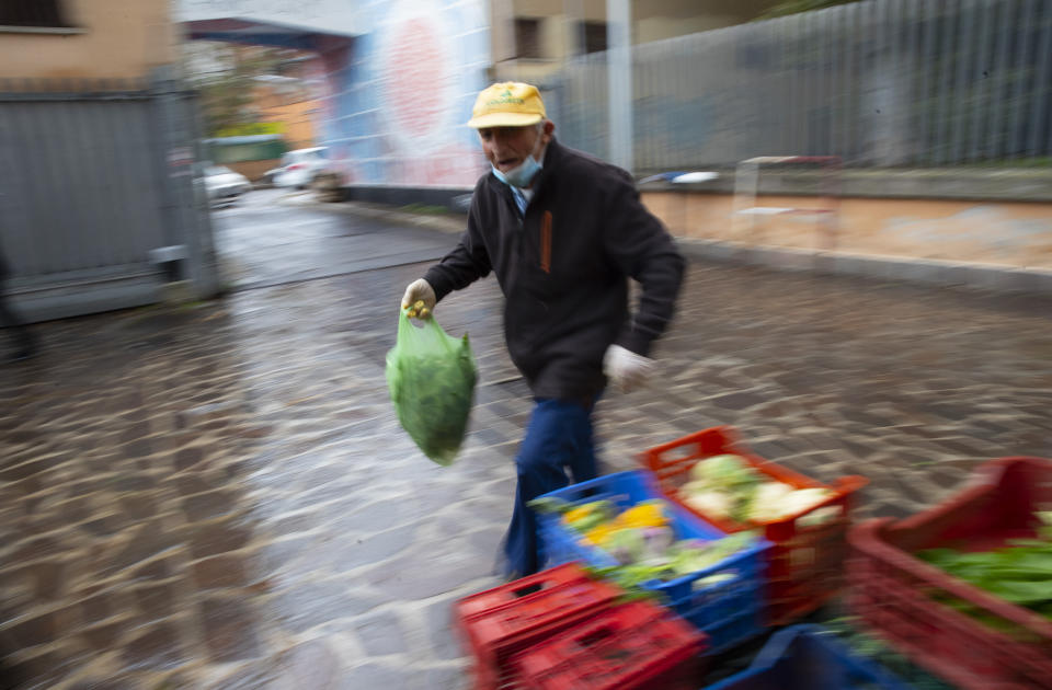Domenico Zoccoli, 80, walks by a fruit and vegetable stand in an open air market where he works, in Rome, Wednesday, Dec. 2, 2020. In Italy, which has the world's second-oldest population, many people in their 70s and older have kept working through the COVID-19 pandemic. From neighborhood newsstand dealers to farmers bring crops to market, they are defying stereotypic labels that depict the old as a monolithic category that's fragile and in need of protection. (AP Photo/Alessandra Tarantino)