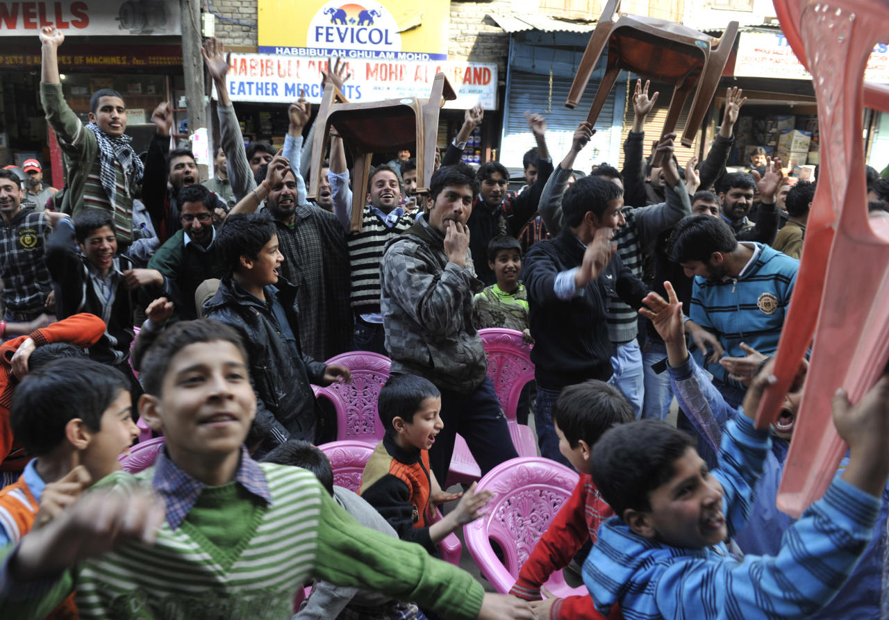 Kashmiris celebrate the dismissal of Indian cricketer Virender Sehwag as they watch a telecast of the Cricket World Cup semi-final match between India and Pakistan on a street in Srinagar on March 30, 2011. Not everyone in India is hoping for a semi-final victory over Pakistan in the cricket World Cup: in Indian Kashmir, allegiance to the rival team reflects bitter feelings in the turbulent region. The match comes at a time when India and Pakistan are again engaging in peace talks with a view to permanently resolving a range of issues that bedevil their relations, including Kashmir. AFP PHOTO/Tauseef MUSTAFA (Photo credit should read TAUSEEF MUSTAFA/AFP/Getty Images)