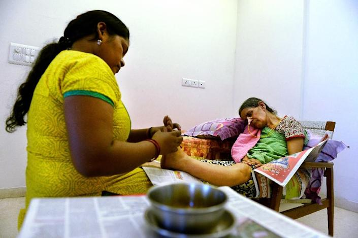 Indian woman Suresh Rani, 62, given an overdose of sodium by doctors at a hospital which resulted in a permanent brain damage, receives a massage at her home in Noida, in New Delhi (AFP Photo/Sajjad Hussain)