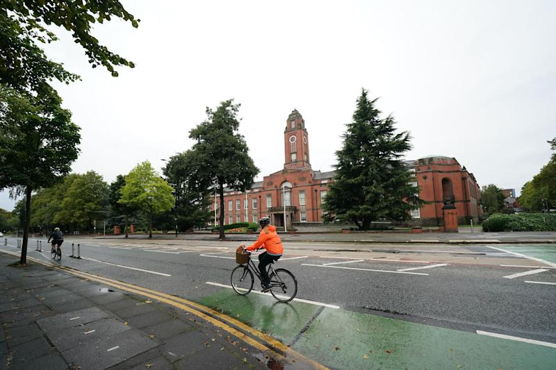 A person cycles past Trafford Town Hall in Greater Manchester (Photo: Xinhua News Agency via Getty Images)