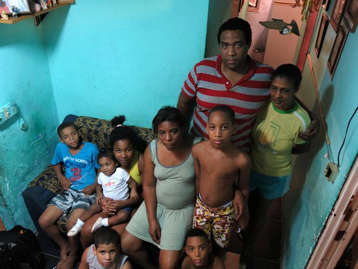 """In this Oct.1, 2013 photo, Amarildo de Souza's sister Maria Lacerda, 52, center, poses for a photo with family members at the Rocinha slum, in Rio de Janeiro, Brazil. De Souza disappeared in July after last being seen in police custody in the Rocinha slum. Investigators said they've recommended to prosecutors that 10 police officers from the slum's """"pacifying"""" unit be charged with de Souza's abduction, torture, death and disappearance of his body. (AP Photo/Bradley Brooks)"""