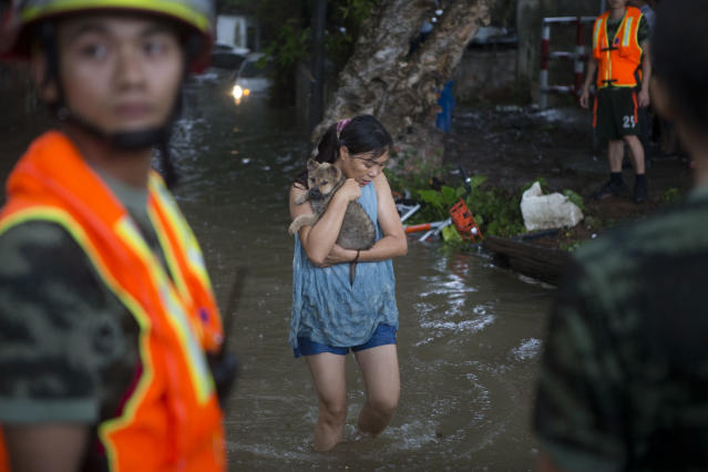 <p>A woman carries her pet in the flooding caused by Typhoon Hato and the astronomical tide on Aug. 23, 2017 in Guangzhou, China. (Photo: Feature China/Barcroft Images/Getty Images) </p>