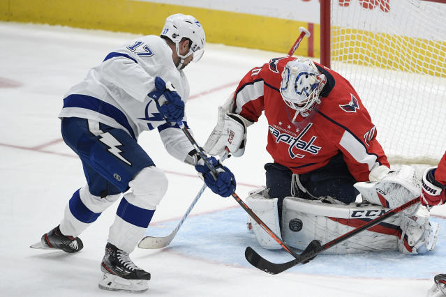 Washington Capitals goaltender Braden Holtby (70) stops the puck next to Tampa Bay Lightning left wing Alex Killorn (17) during the third period of an NHL hockey game, Saturday, Dec. 21, 2019, in Washington. (AP Photo/Nick Wass)