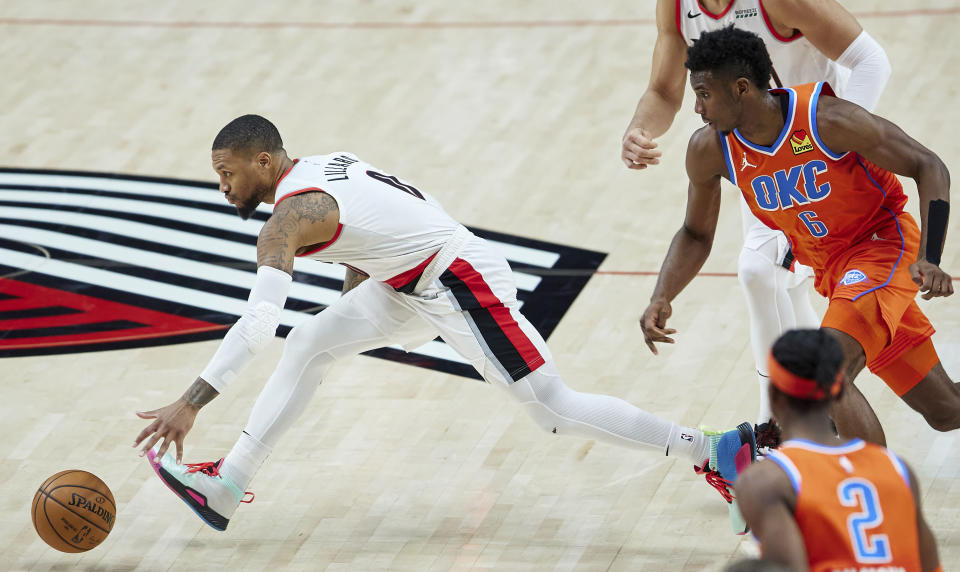 Portland Trail Blazers guard Damian Lillard, left, runs after the ball in front of Oklahoma City Thunder guard Hamidou Diallo during the first half of an NBA basketball game in Portland, Ore., Monday, Jan. 25, 2021. (AP Photo/Craig Mitchelldyer)