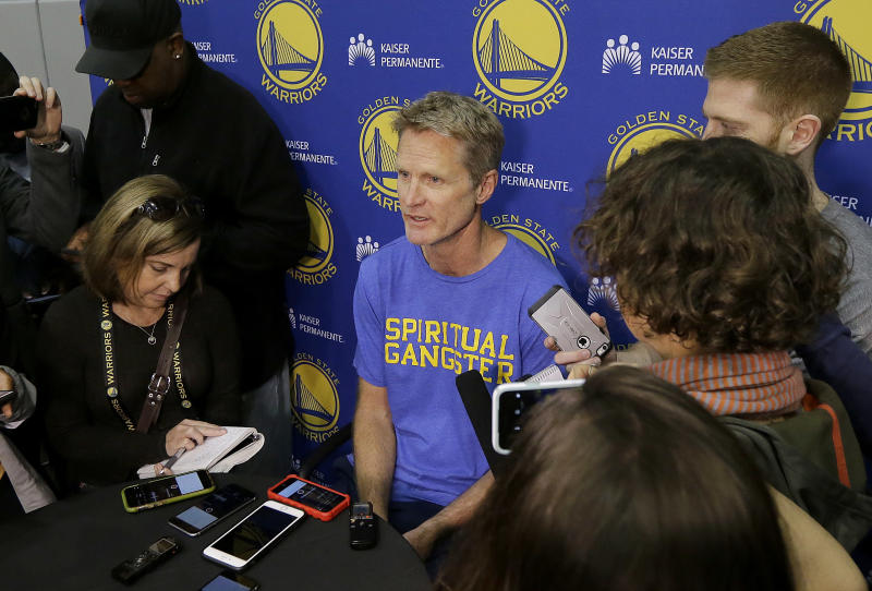 FILE - In this April 7, 2017, file photo, Golden State Warriors head coach Steve Kerr, center, speaks during NBA basketball practice in Oakland, Calif. The Warriors return to the practice court following a day off after their first-round sweep of Portland, with coach Kerr's health status still unclear.  (AP Photo/Jeff Chiu, File)