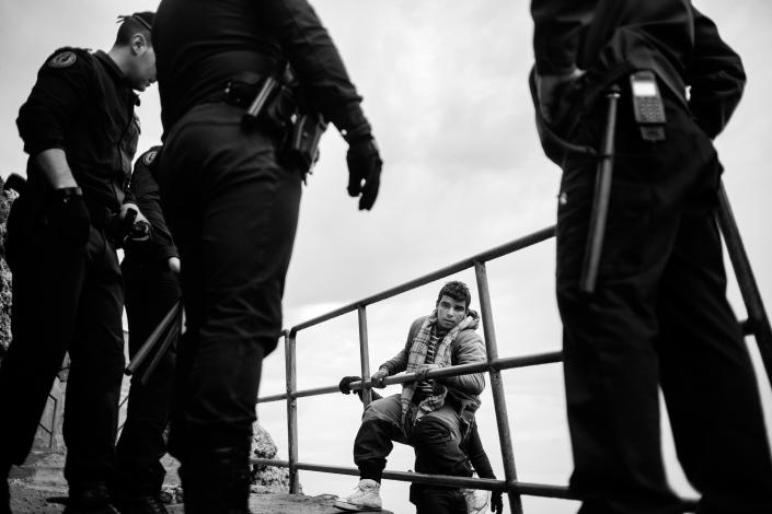 A child of Moroccan origin climbs the wall at the port of Melilla, while the Civil Guard police wait to stop him in 2014. That day the security forces conducted a raid to arrest minors in the port of Melilla. (Photo: José Colón/MeMo for Yahoo News)