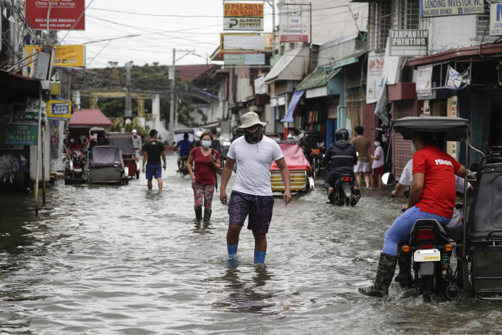 Residents wearing masks to prevent the spread of the coronavirus wade through a flooded road from Typhoon Molave in Pampanga province, northern Philippines on Monday, Oct. 26, 2020. The fast moving typhoon has forced thousands of villagers to flee to safety in provinces. (AP Photo/Aaron Favila)