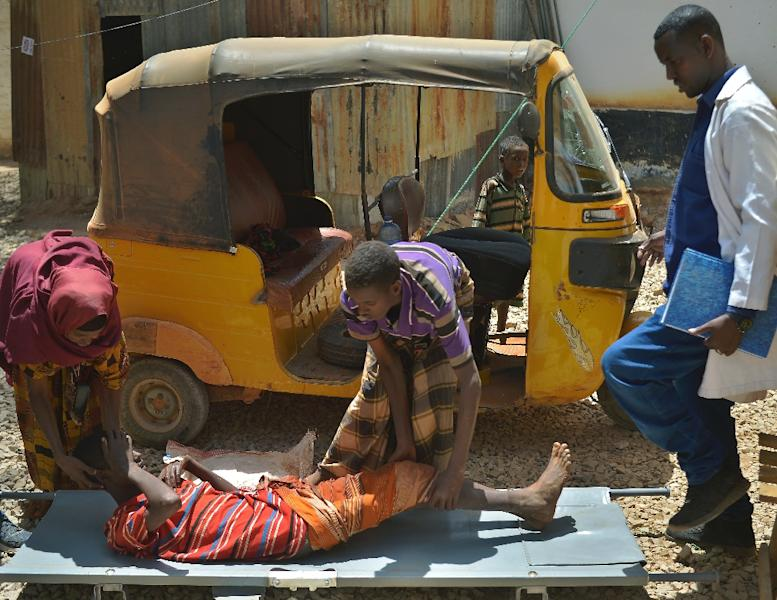 A boy with cholera is helped onto a stretcher as he arrives at the regional hospital in Baidoa town, the capital of the Bay region of southwestern Somalia (AFP Photo/TONY KARUMBA)