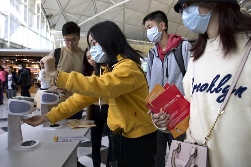 Travelers wearing face masks gather at Hong Kong International Airport in Hong Kong, Tuesday, Jan. 21, 2020. Face masks sold out and temperature checks at airports and train stations became the new norm as China strove Tuesday to control the outbreak of a new coronavirus that has reached four other countries and territories and threatens to spread further during the Lunar New Year travel rush. (AP Photo/Ng Han Guan)