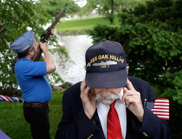 <p>Jim Benning, right, who served as a second class machinist's mate on the USS Oak Hill during the Vietnam War, covers his ears as Chris Moeller, back, of the Sons of the American Legion, takes part of a gun salute during a Memorial Day observance, Monday, May 29, 2017, in Bridgewater, N.J. (Photo: Julio Cortez/AP) </p>