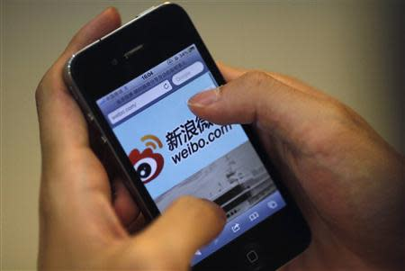 A man uses his phone to visit the Sina Weibo microblogging site in Shanghai, in this file picture taken May 29, 2012. REUTERS/Carlos Barria/Files