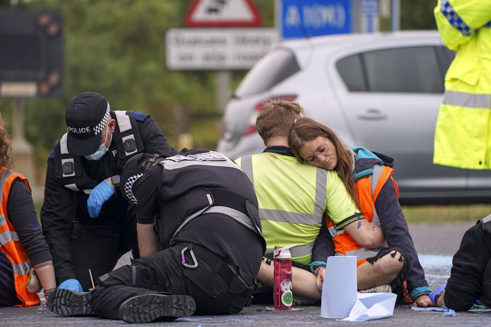 Police officers work to free protesters who had glued themselves to a slip road at Junction 4 of the A1(M), near Hatfield, where climate activists carried out a further action after demonstrations which took place last week across junctions in Kent, Essex, Hertfordshire and Surrey. Picture date: Monday September 20, 2021.