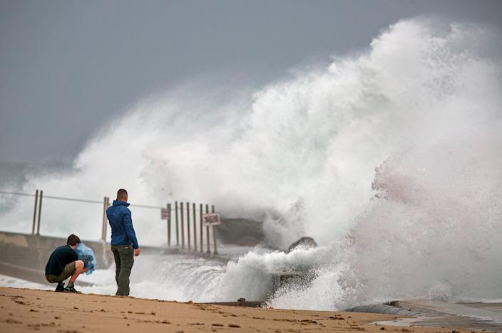 Waves driven by Tropical Storm Isaias crash over the jetty on the north side of the Palm Beach Inlet in Palm Beach Shores Sunday, Aug. 2, 2020.