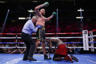Tyson Fury, of England, knocks down Deontay Wilder in a heavyweight championship boxing match Saturday, Oct. 9, 2021, in Las Vegas. (AP Photo/Chase Stevens)