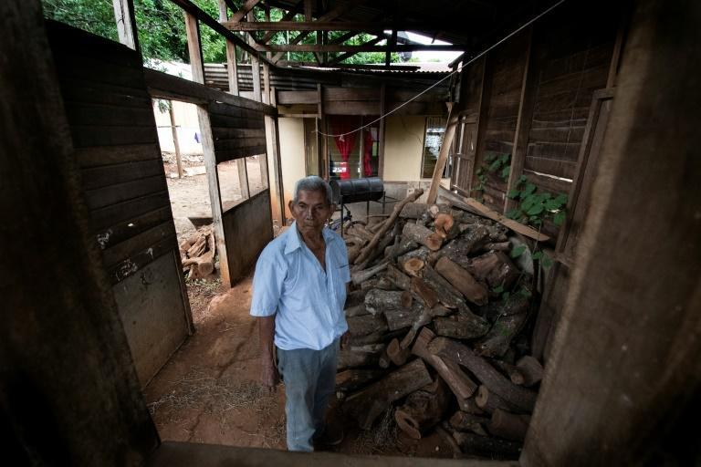 Saturnino Lopez, 94, stands next to a pile of firewood at his home in Nicoya, Costa Rica, on August 27, 2021 (AFP/Ezequiel BECERRA)