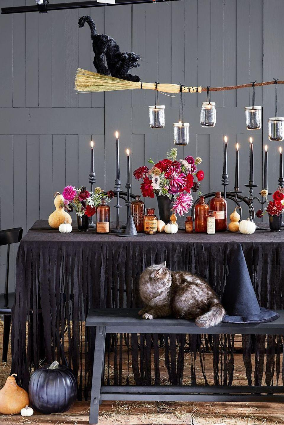 <p>Go all out with apothecary bottles, gourds, flowers and black candles lining the center of your table. A black cat sitting atop a witch's broom suspended from the ceiling takes it over the top.</p>