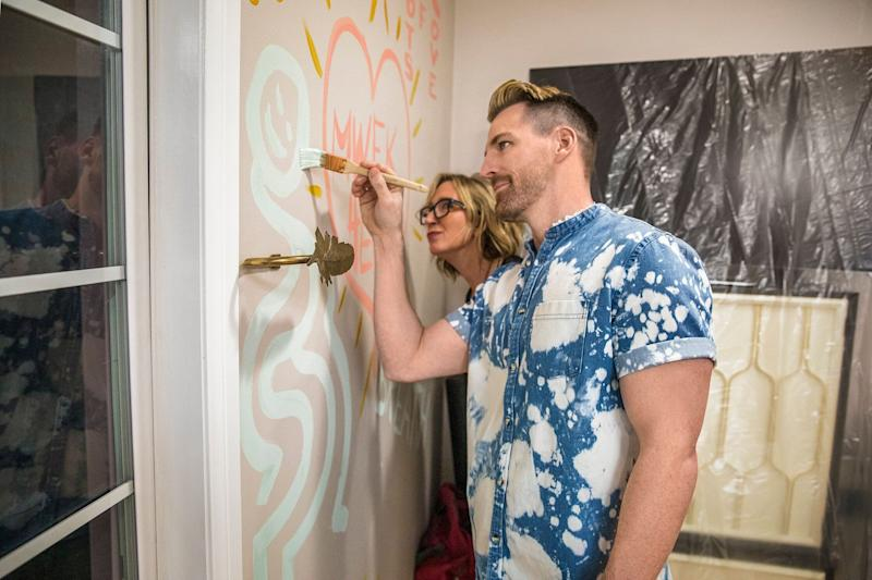 """Orlando Soria and homeowner Kille burn sage in her bedroom while testing out new paint colors by painting ideas they wish to manifest, as seen on """"Unspouse My House."""" (Photo: )"""