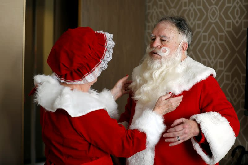 American couple Fred and Kathleen Honerkamp, make adjusts to their Santa Claus outfits as they prepare to visit Jerusalem's Old City together with a group of Santa Clauses from around the world, at their hotel in Jerusalem