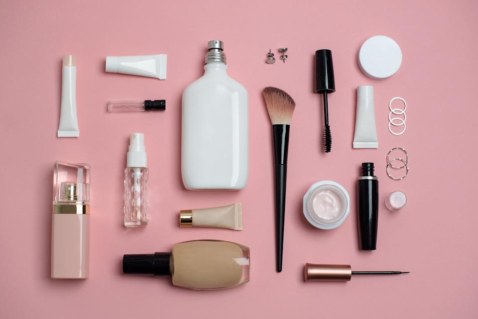 Makeup Bag with variety of beauty products. Eyeliner, makeup brush, perfume, face cream, face powder.