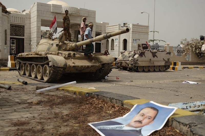 A poster of Yemen's former President Ali Abdullah Saleh lies on the ground as army soldiers and tribesmen loyal to the army gather on a tank in front of the local authority compound in the city of Zinjibar, Yemen after they retook the city from al-Qaida militants, Thursday, June 14, 2012. Airstrikes and clashes intensified in southern Yemen on Wednesday as army troops followed major victories with more pressure on al-Qaida militants holding small towns, according to tribal and military officials. The attacks came a day after Yemeni forces regained control of two major al-Qaida strongholds, Jaar and Zinjibar, which were in the hands of the militants for more than a year. (AP Photo/Hani Mohammed)