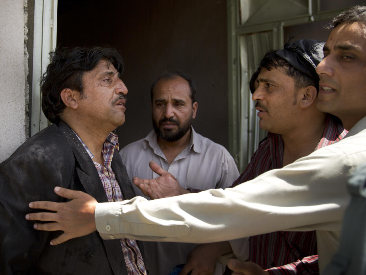 Afghans comfort a man, left, who claims he has lost all his children at the scene where a suicide car bomber attacked a NATO convoy in Kabul, Afghanistan, Thursday, May 16, 2013. A Muslim militant group, Hizb-e-Islami, claimed responsibility for the early morning attack, killing at least six people in the explosion and wounding more than 30, police and hospital officials said. The powerful explosion rattled buildings on the other side of Kabul and sent a pillar of white smoke into the sky in the city's east. (AP Photo/Anja Niedringhaus)