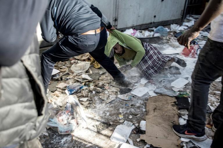 A woman, a suspected looter, is dragged out of a vandalised shop where she was caught by a group of community vigilantes