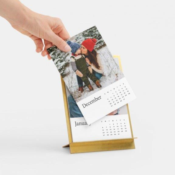 """Just upload 12 of your favorite family snaps, then pick your font and base material of your choice to create a personalized keepsake that will make mom smile all year.  <strong>Buy It! </strong>$55; <a href=""""https://www.artifactuprising.com/photo-calendars/brass-easel-desk-calendar"""">artifactuprising.com</a>"""