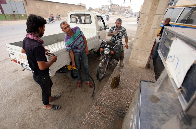 A man fills a vehicle with locally extracted and refined fuel from a makeshift refinery in the northeastern Syrian city of Hasakeh, on July 15, 2015 (AFP Photo/Youssef Karwashan)