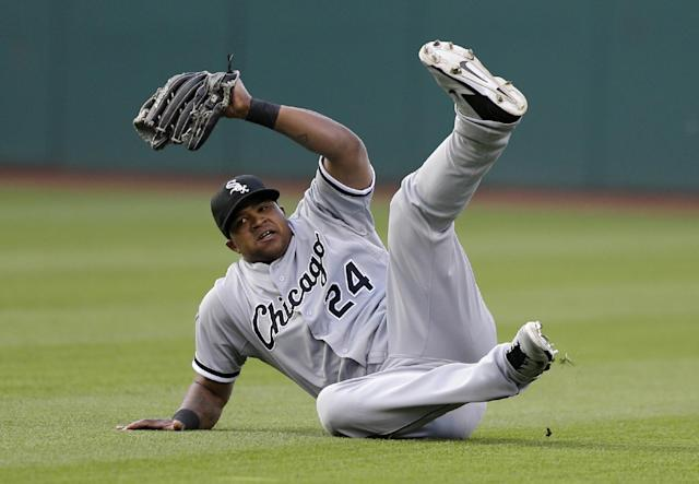 Chicago White Sox's Dayan Viciedo rolls after diving for a ball hit by Cleveland Indians' Lonnie Chisenhall in the third inning of a baseball game, Saturday, May 3, 2014, in Cleveland. Chisenhall was out. (AP Photo/Tony Dejak)